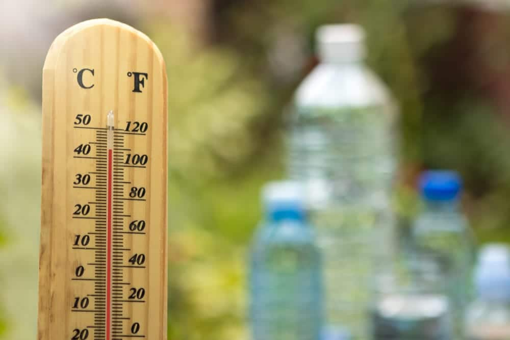 Thermometer reaching 110 degrees F, water bottles in background