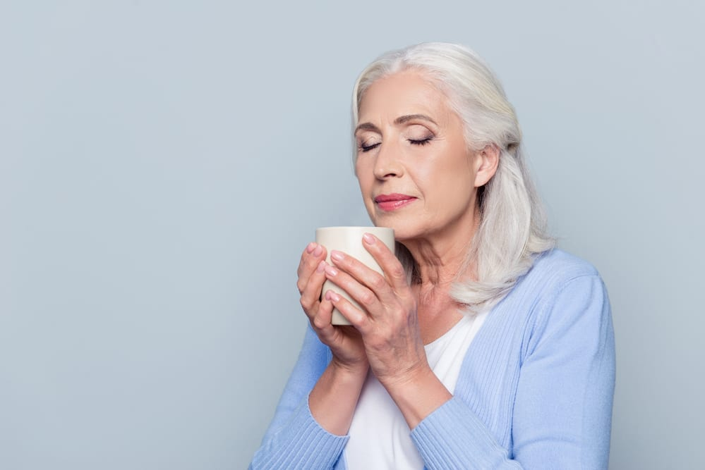 Senior woman smelling cup of coffee, smiling