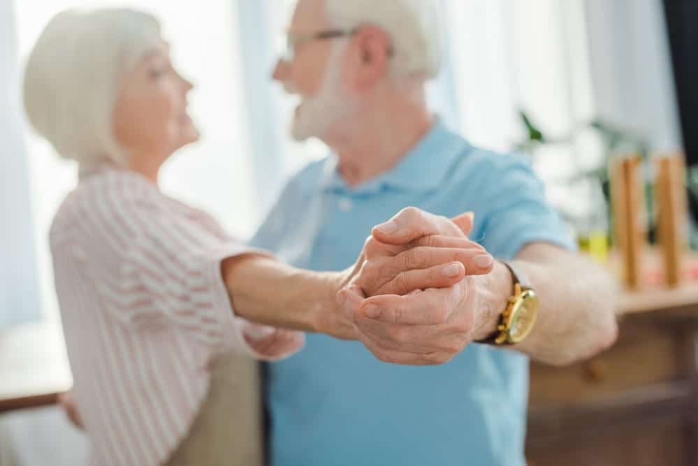 Focus on the hands of a senior couple dancing inside