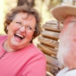 Senior woman laughing outside on bench, senior man in foreground blurry